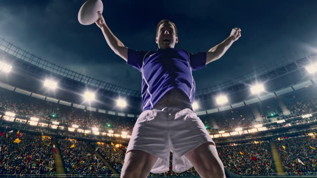 Rugby player jumps with a ball