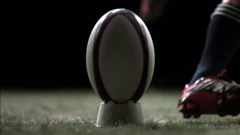 vídeos de stock e filmes b-roll de sm cu rugby player running and kicking ball from tee on wet grass/ auckland, new zealand - râguebi desporto