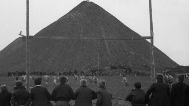vidéos et rushes de montage rugby players kicking, throwing and catching football, running and rolling on field, spectators intently watching, coal mounds beyond / flimby, england, united kingdom - mineur de charbon