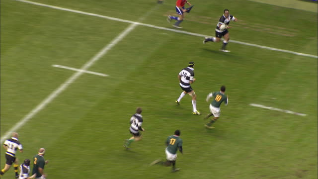 rugby players tackle one another during a game between the barbarians and the south african springboks - tackling stock videos & royalty-free footage
