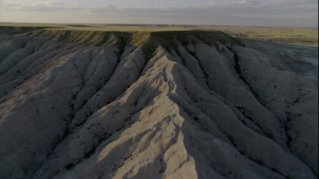 rugged badlands give way to grassy tablelands in south dakota. available in hd. - badlands national park video stock e b–roll