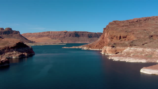 rugged buttes form the shoreline of lake powell. - lago powell video stock e b–roll