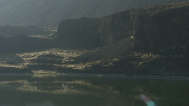 rugged cliffs border a calm lake. available in hd. - seeufer stock-videos und b-roll-filmmaterial