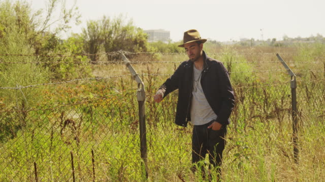 rugged man leaning on wire fence outdoors - puerto rican ethnicity stock videos & royalty-free footage