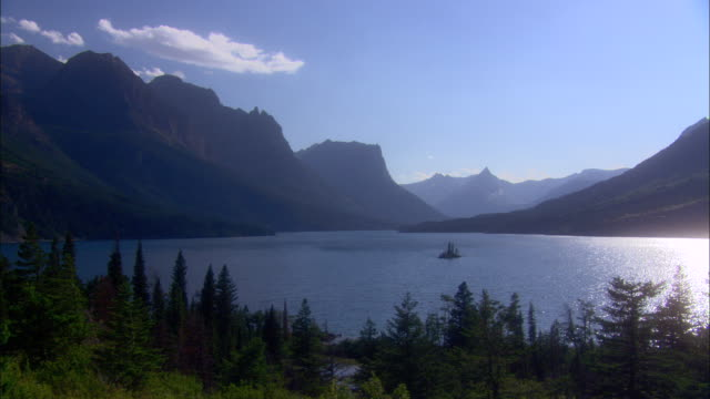 vídeos de stock, filmes e b-roll de a rugged mountain range surrounds a lake in glacier national park. - glacier national park us