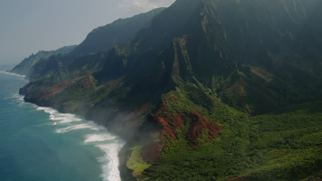rugged mountains and lush foliage line the na pali coast in hawaii. - na pali coast state park stock videos & royalty-free footage