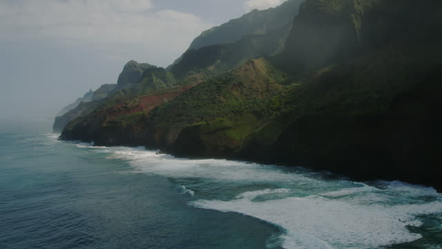 rugged mountains and lush foliage line the na pali coast in hawaii. - insel kauai stock-videos und b-roll-filmmaterial