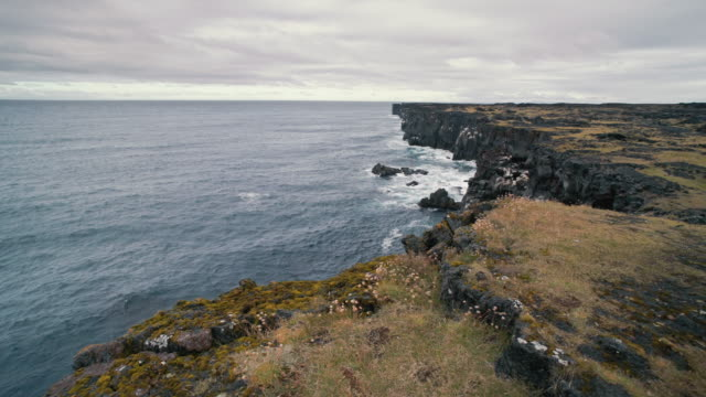 stockvideo's en b-roll-footage met rugged sea cliffs near svortuloft lighthouse in western iceland - ruw