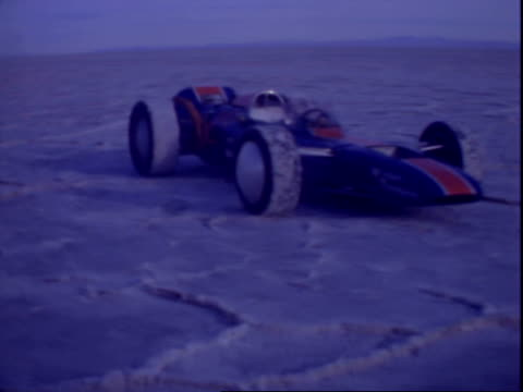rugged terrain and mountains surrounding salt flats / circular traveling shots of thompson indy race car parked on salt flat / thompson indy race car... - bonneville salt flats stock videos and b-roll footage
