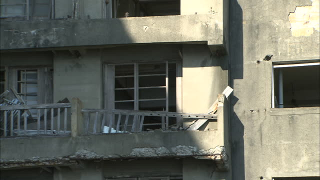 ruined balconies of hashima primary school provide a lookout into a dirt lot. - 荒廃した点の映像素材/bロール