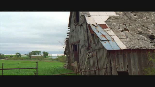 ms, pan, ruined barn and field, car driving fast on rural road - anamorphic stock videos & royalty-free footage