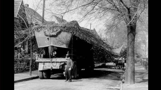 vídeos de stock, filmes e b-roll de wwii ruined building in small town amphibious landing craft stored on town square / soldiers preparing landing craft with camouflage playing catch... - navio de desembarque de doca