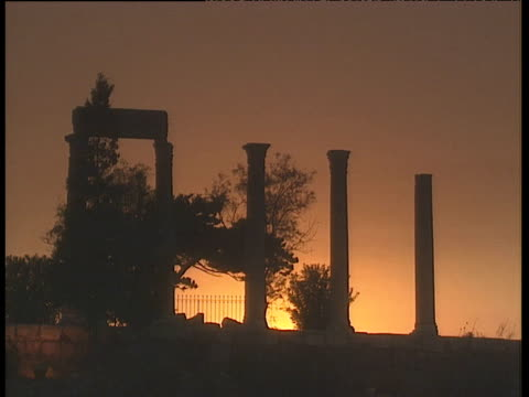 ruined columns silhouetted against orange sunset lebanon - old ruin stock videos and b-roll footage