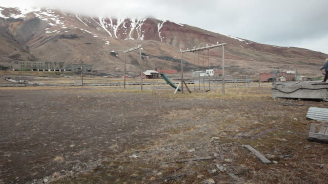 Ruined kids playground with seagulls flying around in Pyramiden, a Soviet Ghost Town on the archipelago of Svalbard