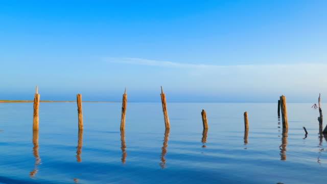 vídeos de stock, filmes e b-roll de cais de madeira arruinada no lago salgado - vista do mar
