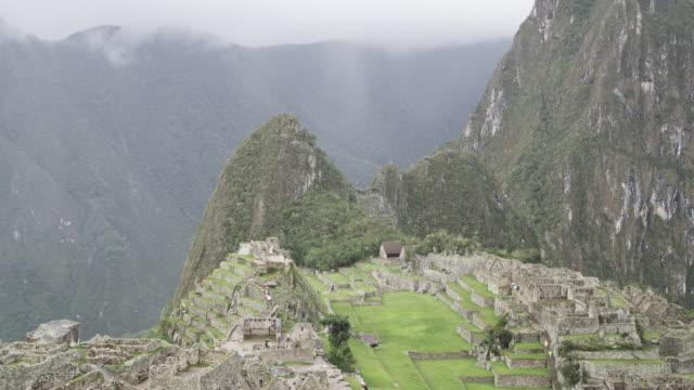 ruins cover a mountainside in machu picchu. - machu picchu stock videos and b-roll footage
