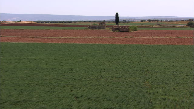 ruins of a farmhouse stand out amidst lush crops and and a plowed field. - masseria video stock e b–roll