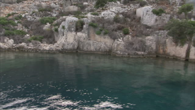 ruins of an ancient city overlook calm, clear water. - archeologia video stock e b–roll