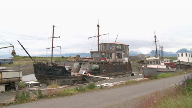 """run down and rusted metal fishing boat with three tier wooden cabin dry-docked at homer boat harbor on homer spit, other boats also dry-docked, snow capped mountains of kachemak bay state park and wilderness park in background."" - homer alaska stock videos & royalty-free footage"