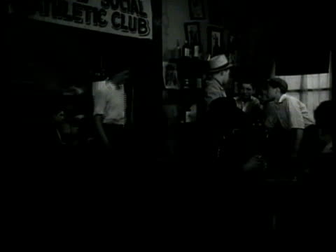 vidéos et rushes de run down buildings clothes hanging on wires to dry children in playground fg. int banner 'athletic club' men mingling in groups. men drinking playing... - 1940