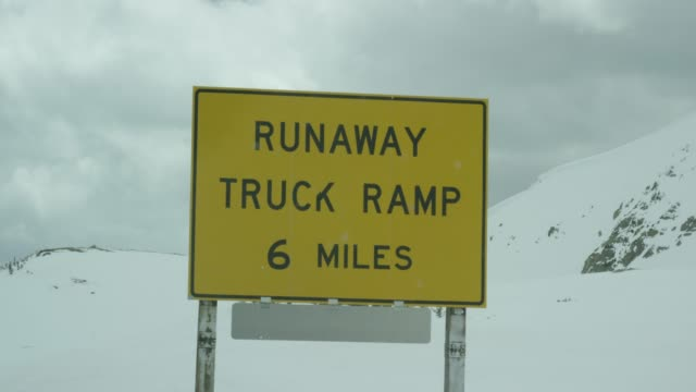 """runaway truck ramp, 6 miles"" caution road sign in the rocky mountains of colorado under an overcast sky in winter - placard stock videos & royalty-free footage"