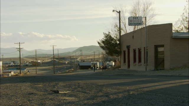 WS Rundown bar motel, empty street, and single person walking in ghost town / Silver Peak, Nevada, USA