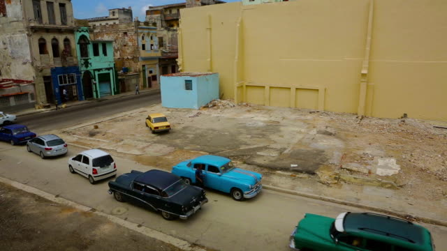 rundown buildings with vintage cars driving around