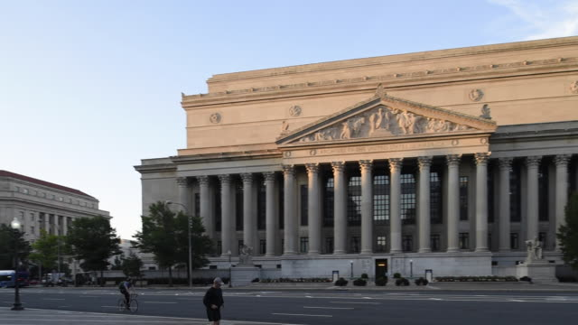 a runner and bicyclist move past national archives building early in the day. - national archives washington dc stock videos and b-roll footage