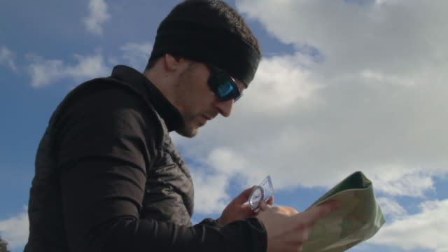 runner checking his compass and map. - cartography stock videos & royalty-free footage
