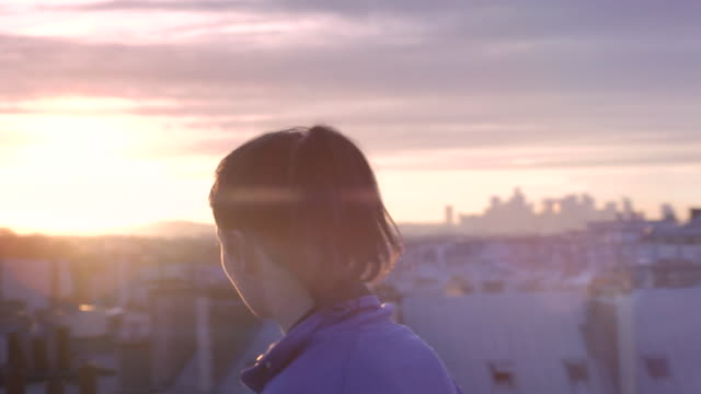vidéos et rushes de runner girl wearing headphones with a paris city view at sunset - toit