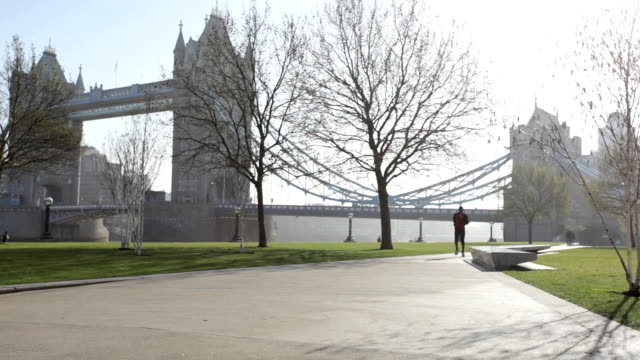 runner in park in front of tower bridge, london, uk - tower of london stock videos and b-roll footage