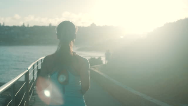 runner in the sunset (slow motion) - one mid adult woman only stock videos & royalty-free footage