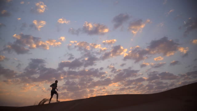 Runner jogging over desert dunes at sunset