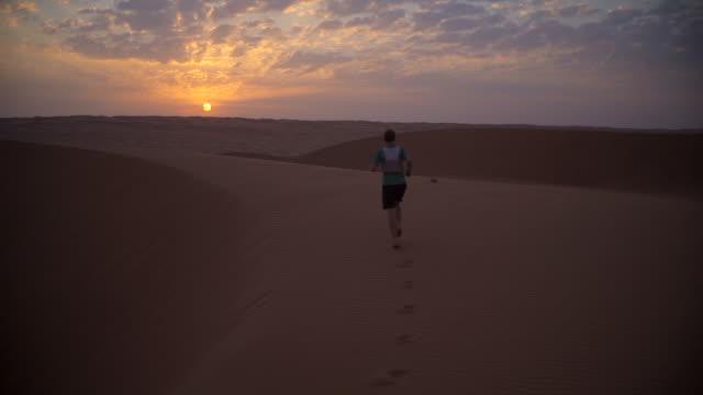 Runner jogging over desert dunes at sunset