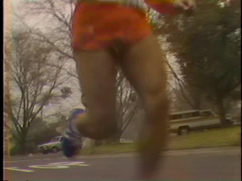 runner jogs along an asphalt street. - jogging stock videos & royalty-free footage