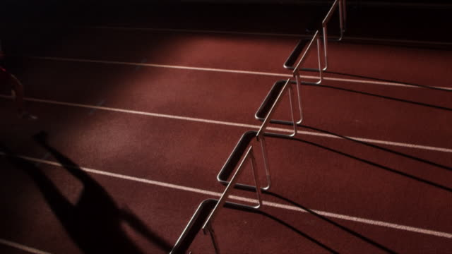 A runner jumps over a hurdle on a track.