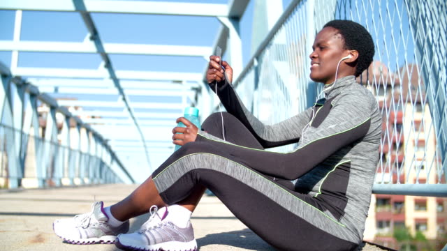 vídeos y material grabado en eventos de stock de hd: runner escuchando música y de agua potable. - corredora de footing