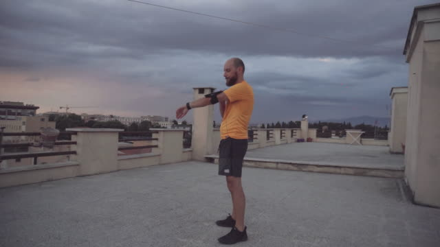 runner man stretching on the roof terrace - wearable computer stock videos & royalty-free footage
