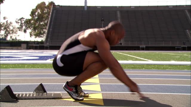 a runner puts his feet into starting blocks before sprinting away. - blocco di partenza per l'atletica video stock e b–roll