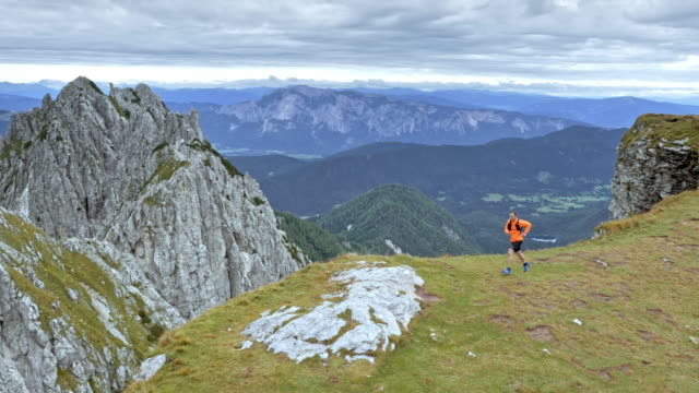 aerial runner running a marathon along the edge of a ridge high in the mountains - tracking shot stock videos & royalty-free footage