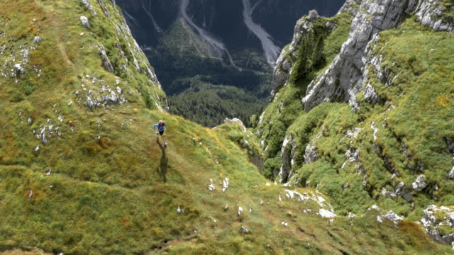 aerial runner running on a mountain top overlooking the valley below and the surrounding mountains - slovenia stock videos & royalty-free footage