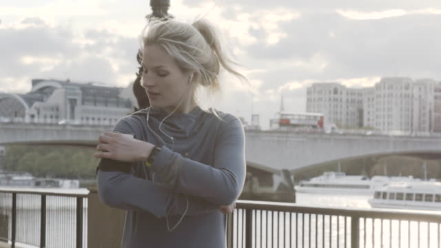 runner running on embankment, stops to look at phone and carries on running. - jogging stock videos & royalty-free footage
