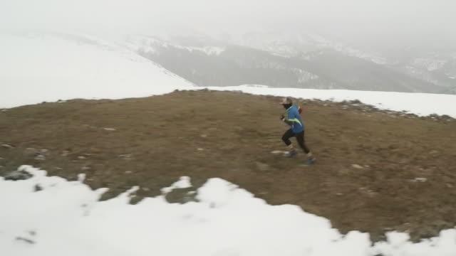Runner running over a snowy mountain aerial shot