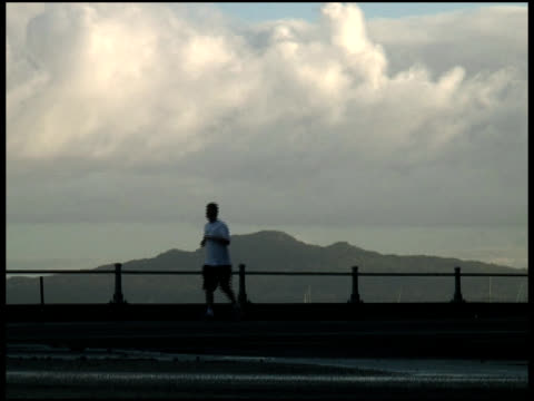 stockvideo's en b-roll-footage met runner silhouetted in front of perfect volcanic island. - breedbeeldformaat