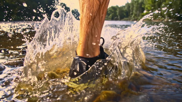 SLO MO Runner splashing in the river