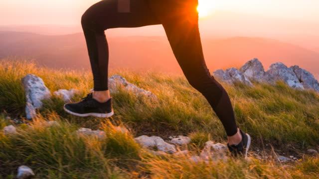 vídeos de stock, filmes e b-roll de corredor de esportes treinamento nas montanhas ao pôr do sol - colina acima