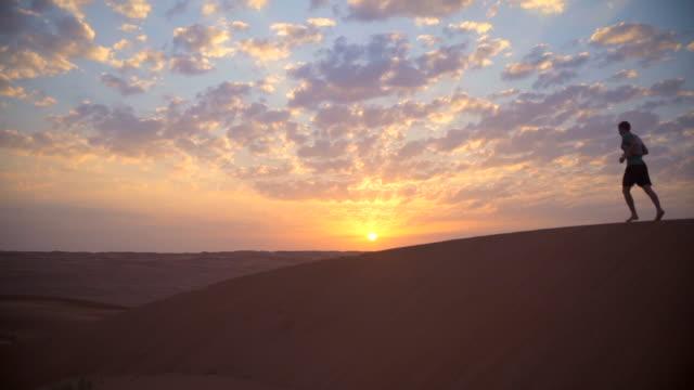Runner sprints over desert dunes at sunset