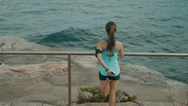 Läufer, die Dehnung in der Nähe des Ozeans