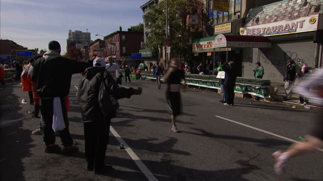 A runner takes a cup of water from a volunteer during a race in New York City.