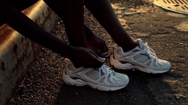 vídeos de stock, filmes e b-roll de runner tying her shoelaces - desempenho atlético